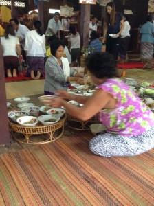 村人たちからの寄進されたおかずを配膳する村人