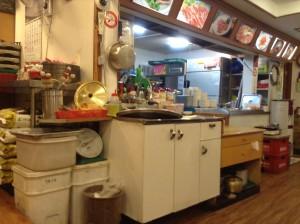 ソウル・カルビ食堂。カウンター右側にキムチなどのおかずが大きな容器に入れられている。おかわりは自由に取ってもOKとのこと。