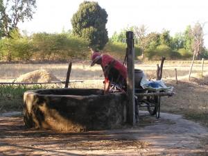 村の外れの井戸から水を汲み上げる村人