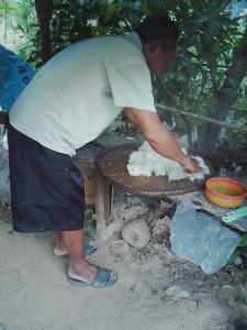 蒸しあがったカオニアオを木の棒で混ぜながら蒸らす